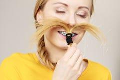 Mujer que hace el bigote fuera del pelo rubio Foto de archivo libre de regalías