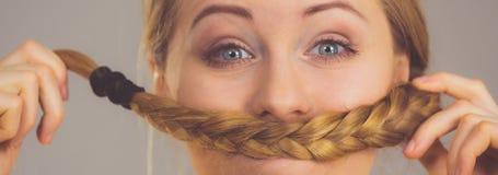 Mujer que hace el bigote fuera del pelo rubio Imagen de archivo libre de regalías