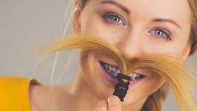 Mujer que hace el bigote fuera del pelo rubio Imágenes de archivo libres de regalías