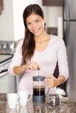 Mujer que hace el café en cocina Foto de archivo