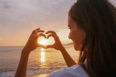 Mujer que hace el corazón de manos en la puesta del sol Foto de archivo libre de regalías