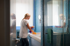 Mujer que hace el cuarto de baño de las tareas y de la limpieza en el país Imagen de archivo libre de regalías
