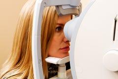 Mujer que hace el examen de ojo terminar Imagenes de archivo