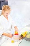 Mujer que hace el jugo de la mañana en cocina Imagenes de archivo