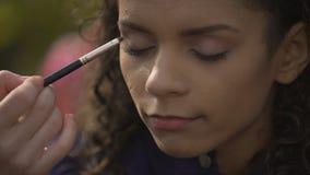 Mujer que hace el maquillaje ahumado de los ojos, preparando a la actriz hermosa para el tiroteo de la película almacen de video
