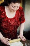 Mujer que hace el pan en su puerta principal imagen de archivo