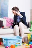 Mujer que hace el quehacer doméstico y que llama el teléfono móvil el mismo tiempo Fotos de archivo