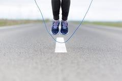 Mujer que hace el salto roping en un campo de deportes imagen de archivo