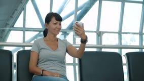 Mujer que hace el selfie en la zona de espera del aeropuerto almacen de metraje de vídeo