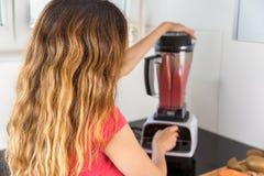 Mujer que hace el smoothie de la fruta Fotos de archivo