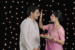 Mujer que hace el tilak de su marido en Diwali