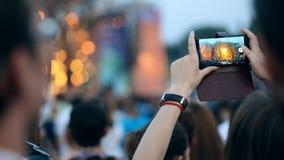 Mujer que hace el vídeo con concierto de la música en festival al aire libre en su smartphone almacen de video