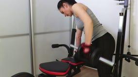 Mujer que hace entrenamiento de la aptitud con las pesas de gimnasia para los músculos traseros almacen de metraje de vídeo
