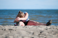 Mujer que hace estirando ejercicio en la playa Fotografía de archivo libre de regalías