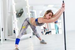 Mujer que hace estirando el ejercicio para los tendones de la corva y la parte posterior que inclinan el barbell que se sostiene  Foto de archivo