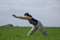 Mujer que hace estirar al aire libre en el campo Foto de archivo libre de regalías