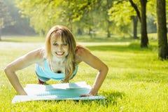 Mujer que hace flexiones de brazos en parque de la mañana Foto de archivo