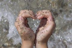 Mujer que hace forma del corazón en la playa Imagenes de archivo