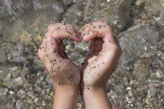 Mujer que hace forma del corazón en la playa Imagen de archivo libre de regalías