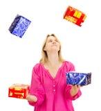 Mujer que hace juegos malabares con algunos regalos coloridos Imágenes de archivo libres de regalías