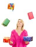 Mujer que hace juegos malabares con algunos regalos coloridos Imagenes de archivo