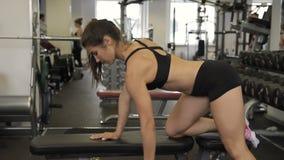 Mujer que hace la barra de la pesa de gimnasia con una mano mientras que se coloca en la cuesta almacen de video