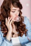 Mujer que hace la burbuja con el chicle Imagenes de archivo