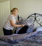 Mujer que hace la cama Fotos de archivo libres de regalías