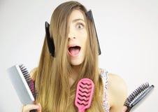 Mujer que hace la expresión divertida con los peines y los cepillos en su pelo largo Fotografía de archivo libre de regalías