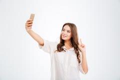 Mujer que hace la foto del selfie en smartphone mientras que muestra la muestra de la victoria Foto de archivo