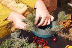 Mujer que hace la guirnalda del advenimiento de la Navidad Fotos de archivo