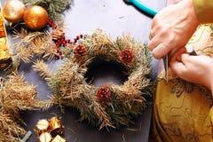 Mujer que hace la guirnalda del advenimiento de la Navidad Foto de archivo