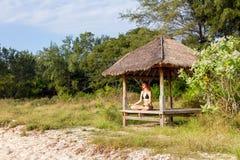Mujer que hace la meditación de la yoga en gazebo tropical Imagenes de archivo