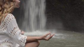Mujer que hace la meditación que se sienta en la cascada en las zonas tropicales metrajes