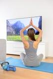 Mujer que hace la meditación casera de la yoga delante de la TV Imagenes de archivo
