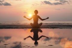 Mujer que hace la meditación en la playa del mar Yoga Fotos de archivo
