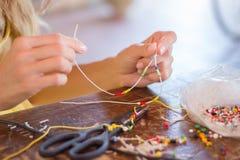 Mujer que hace la pulsera en casa Foto de archivo libre de regalías
