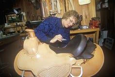 Mujer que hace la silla de montar occidental por encargo, talabartería de tres bifurcaciones, Montana Imagen de archivo libre de regalías