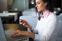 Mujer que hace las compras en línea en el café, números que mecanografían de la tarjeta de crédito de la tenencia en vista latera