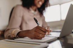Mujer que hace las notas que miran el ordenador portátil que trabaja de hogar imagen de archivo