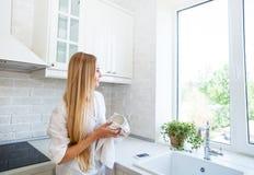 Mujer que hace lavarse para arriba en la cocina imágenes de archivo libres de regalías