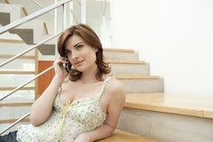 Mujer que hace llamada de teléfono en escalera Fotos de archivo libres de regalías