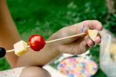 Mujer que hace los aperitivos que ponen aceitunas del queso tomates en de madera Fotografía de archivo libre de regalías
