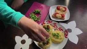 Mujer que hace los bocadillos Adorna el plato acabado con las cebollas verdes tajadas almacen de metraje de vídeo