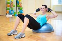 Mujer que hace los ejercicios para los músculos abdominales en bola del bosu Fotografía de archivo libre de regalías