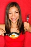 Mujer que hace los huevos para el desayuno Fotos de archivo