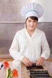 Mujer que hace los rodillos de sushi japoneses Imagenes de archivo