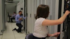 Mujer que hace mantenimiento con PC de la tableta almacen de video