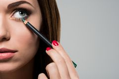 Mujer que hace maquillaje con el lápiz cosmético imagenes de archivo