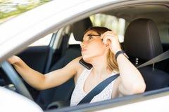 Mujer que hace maquillaje en coche móvil imagen de archivo libre de regalías